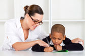 Caring elementary teacher helping schoolboy — Stock Photo