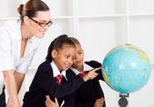 Elementary geography teacher and students looking at globe — Stock Photo