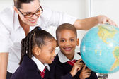 Elementary geography teacher and students — Stock Photo