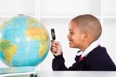 Primary schoolboy looking at globe — Stock Photo