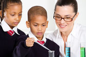 Science teacher and students in lab — Stock Photo