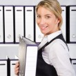 Young happy businesswoman searching file in office — Stock Photo