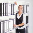 Young happy businesswoman searching file in office — Stock Photo #11141023