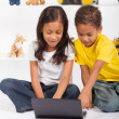 Brother and sister playing laptop computer — Stock Photo