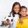 Brother and sister holding a soccer ball — Stock Photo