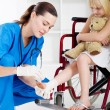 Caring nurse bandage little girl's ankle — Stock Photo