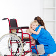 Stock Photo: Little girl patient on wheelchair hugging doctor
