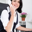 Businesswoman answering telephone in office — Stock Photo