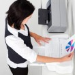 Businesswoman using fax machine in office - Stock Photo