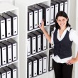 Businesswoman standing next to office files — Stock Photo