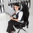 Stock Photo: Young businesswoman looking files