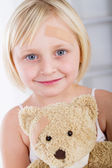 Little girl with band-aid on her face holding a teddy bear — Stock Photo