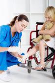 Caring nurse bandage little girl's ankle — Stock Photo