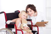 Caring nurse and smiling little girl patient — Stock Photo