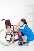 Little girl patient on wheelchair hugging doctor — Stock Photo