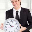 Young businessman holding a clock in office — Stock Photo #11280533
