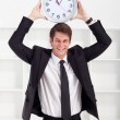 Young businessman holding a clock in office — Stock Photo #11280546