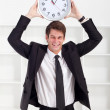 Young businessman holding a clock in office — Stock Photo