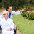 Stock Photo: Female nurse taking disabled senior patient for a walk