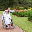 Female nurse taking disabled senior patient for a walk — Stock Photo