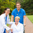 Caring medical doctor, nurse and senior patient outdoors — Stock Photo