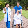 Stock Photo: Caring medical workers and patient