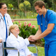 Friendly male doctor greeting recovering senior patient — Stock Photo