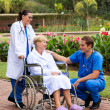 Male doctor talking to senior patient in hospital garden — Stock Photo