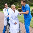Young caring doctor and nurse helping senior patient get up from wheelchair — Stock Photo