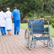 Caring doctor and nurse helping senior patient get up from wheelchair and walk — Stock Photo