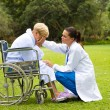 Stock Photo: Young doctor comforting a lonely disabled senior patient outdoors