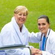 Caring friendly doctor and happy senior patient outdoors — Stock Photo