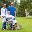 Group portrait of doctor, nurse and senior patient in hospital garden — Stock Photo
