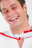 Mannen i badrummet sätta tandkräm på tandborsten — Stockfoto