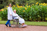 Caring female doctor push senior patient on wheelchair outdoors — Stock Photo