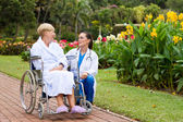 Caring female nurse talking to disabled senior patient — Stock Photo
