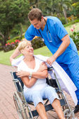 Cuidado médico dando su chaqueta a un paciente senior — Foto de Stock