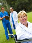 Beautiful senior patient sitting on wheelchair in hospital garden — Stock Photo