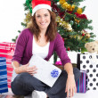 Stock Photo: Happy young woman under a Christmas tree