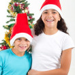 Happy sister and brother in front of christmas tree — Stock Photo