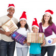 Happy family of four holding christmas presents on white — Stockfoto