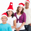 Happy multiracial family of four wearing santa hats — Stock Photo #11308031