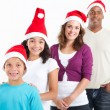 Happy multiracial family of four wearing santa hats — Stock Photo