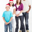 Happy multiracial family of four wearing santa hats — Φωτογραφία Αρχείου
