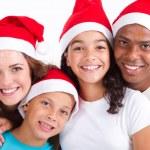 Happy multiracial family of four wearing santa hats — Stock Photo