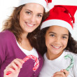 Happy mother and teen daughter holding christmas candy cane — Stock Photo