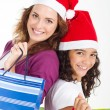 Happy mother and daughter with Christmas shopping bags — Stock Photo