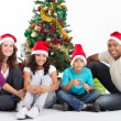 Happy family sitting near Christmas tree — Stock Photo #11308081