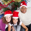 Happy family sitting near Christmas tree — Stock fotografie