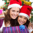 Happy mother and daughter holding Christmas gifts — Stock Photo